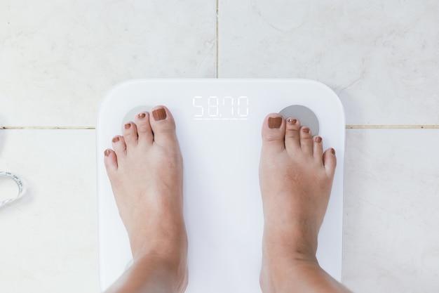 Voeten staan op elektronische weegschaal voor gewichtscontrole. meetinstrument in kilogram voor een dieetcontrole.