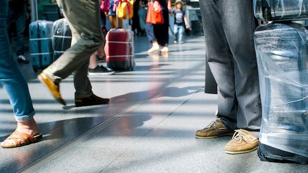 Voeten toeristen met bagage die in een lange rij staan bij de luchthaventerminal.