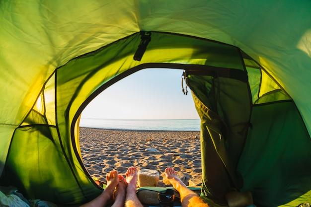Voeten uit een tent met uitzicht op de kust