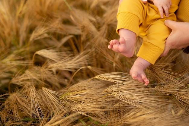 Voeten van babyjongen op rijpe tarwe close-up