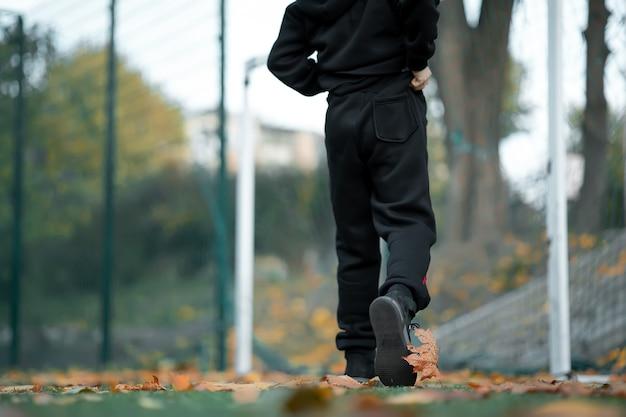 Voeten van een jongen die over het voetbalveld loopt.