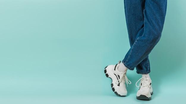 Voeten van een kind in witte sneakers met veters en wijde spijkerbroek op een blauwe ondergrond