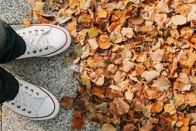 Voeten van een meisje in spijkerbroek en witte sneakers op de stoep met gele herfstbladeren