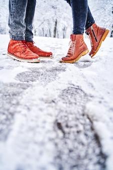 Voeten van een paar op een besneeuwde stoep in bruine laarzen