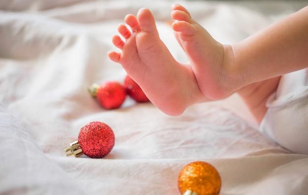 Voeten van een pasgeboren baby op een wit met kerstmisspeelgoed