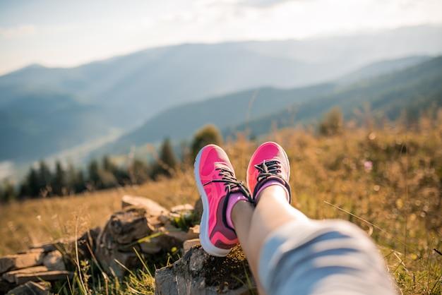 Voeten van een sportmeisje die in de bergen ontspannen