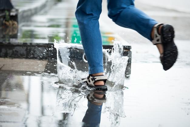 Voeten van een vrouw die in de regen loopt