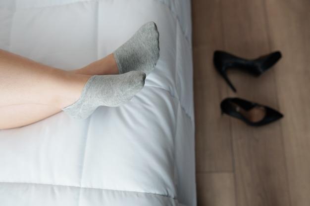 Voeten van een vrouw die op bed ligt na de hele dag op hoge hakken te hebben gelopen, van bovenaf te bekijken