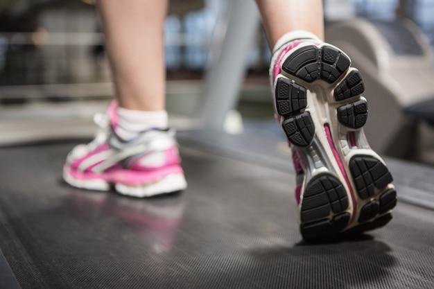 Voeten van een vrouw op een loopband in een sportschool