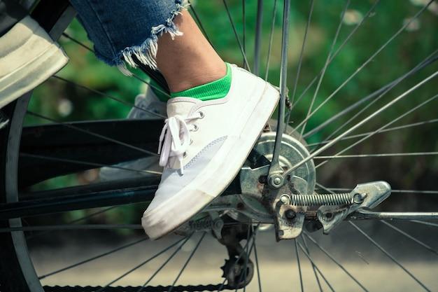 Voeten van jonge vrouw op een fiets