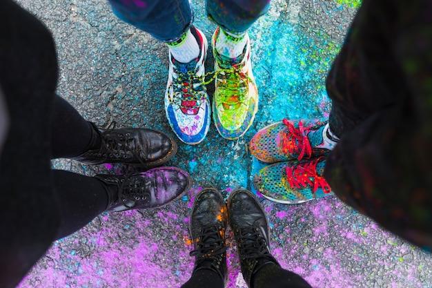 Voeten van mensen die zich op weg in kleurrijke verf bevinden