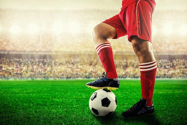 Voeten van rode teamvoetballer op voetbalbal voor start in het stadion