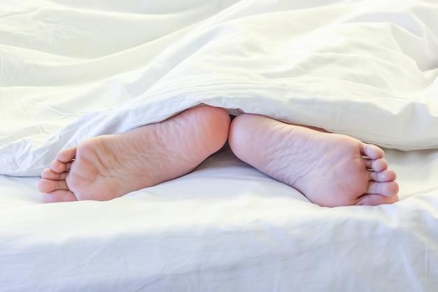 Voeten van slapende vrouw in witte bedruimte
