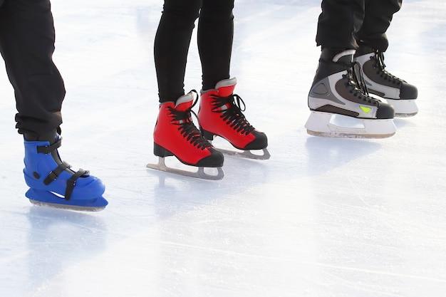 Voeten van verschillende mensen die schaatsen op de ijsbaan