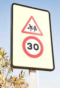 Voetgangers waarschuwingsbord met 30 snelheidsbeperkingsteken tegen blauwe hemel
