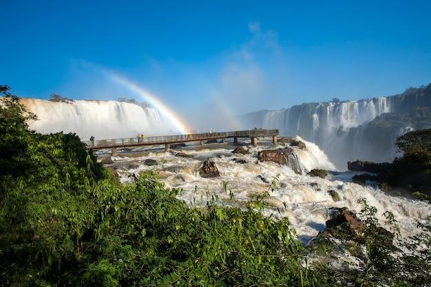 Voetgangersbrug en regenboog in iguazu valt nationaal park