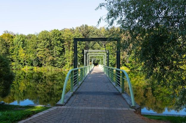 Voetgangersbrug over de rivier in de rivier en bomen en weerspiegeling in het water.
