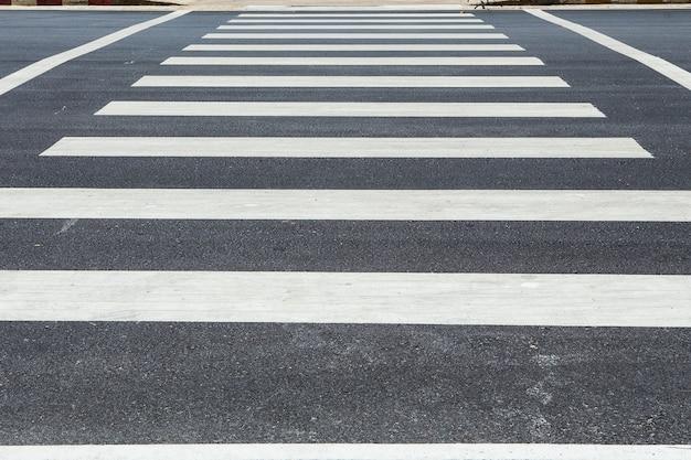 Voetgangersoversteekplaats, de gestreepte manier van de verkeersgang op asfaltweg
