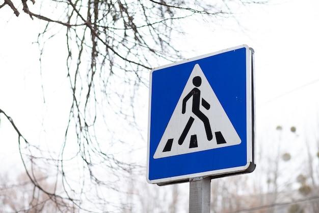 Voetgangersoversteekplaats teken. close-up van voetgangersoversteekplaats teken tegen een hemel.