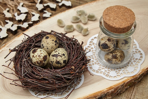 Vogeleieren in een nest, eieren in een pot, houten hazen en wilgenknoppen op een houten zaag. pasen concept
