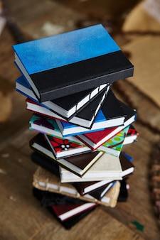 Vogelperspectief van de veelkleurige stapel kleine handgemaakte boeken op een houten oppervlak