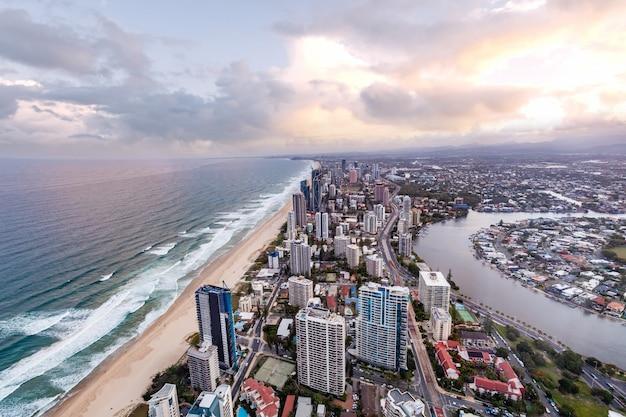 Vogelperspectief van gold coast-stadshorizon en oceaan bij zonsondergang