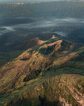 Vogelperspectief van heuvels bedekt met groen en mist onder het zonlicht - perfect voor behang