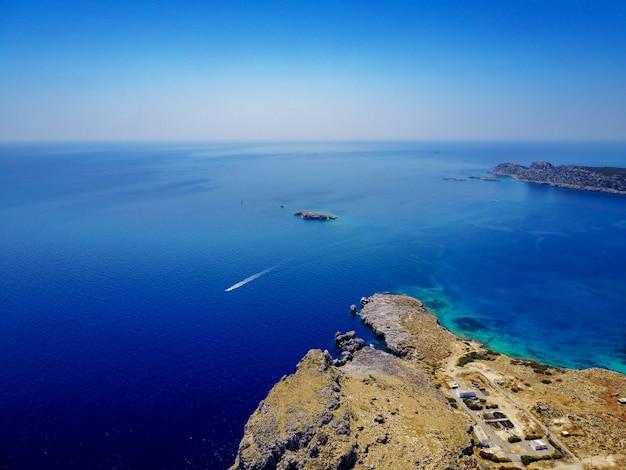 Vogelperspectief van mediterrane kustlijn met koraalzee en alleen speedboot.