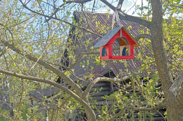 Vogelvoeder op een boom, tegen de achtergrond van een houten schuur.