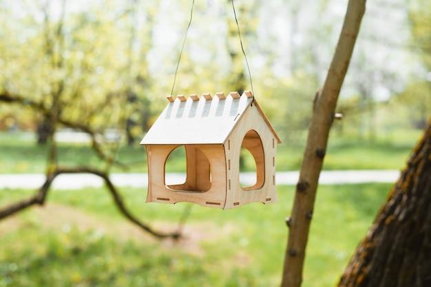 Vogelvoederhuis in de vorm van een huisje dat aan een boom hangt. park zonnige zomerdag. close-up van een klein houten vogelhuisje.