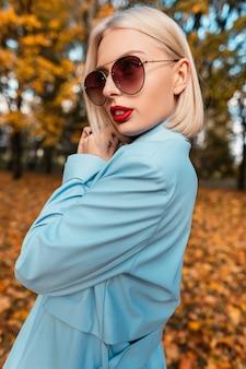 Vogue portret van een mooie vrouw met een kort kapsel en rode lippen in modieuze kleding met een blauwe jas en een zonnebril op de natuur in een herfstpark met geel blad