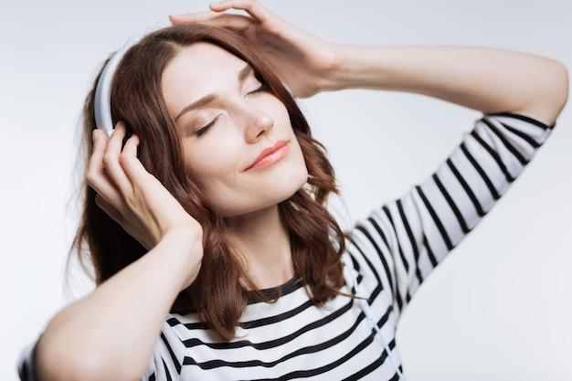 Vol dromen. charmante dromerige jonge vrouw, luisteren naar de muziek in de koptelefoon en haar ogen sluiten in verrukking