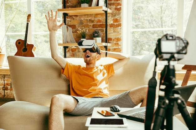 Vol emoties. blanke mannelijke blogger met professionele camera opname videoreview van vr-bril thuis