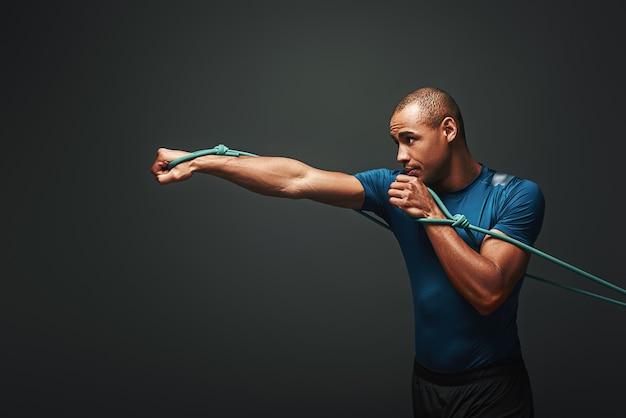Vol energie sportman trainen met weerstandsband over donkere achtergrond