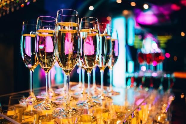 Vol glas champagne in een nachtclub. veel glazen champagne op de bar. bubbels champagne in een glas.