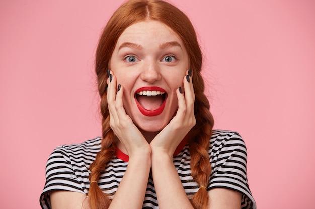 Vol met positieve emoties vrolijk roodharig meisje met twee vlechten houdt de handen dicht bij haar gezicht en opent mond wijd van opwinding, met rode lippen, witte gezonde tanden, geïsoleerd op roze muur