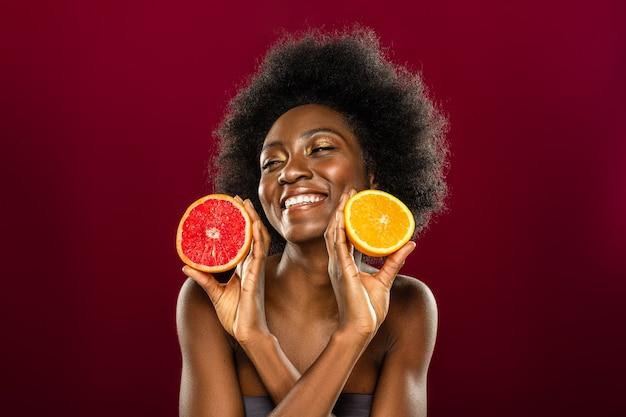 Vol met vitamines. opgetogen, aardige vrouw die glimlacht terwijl ze je fruithelften laat zien