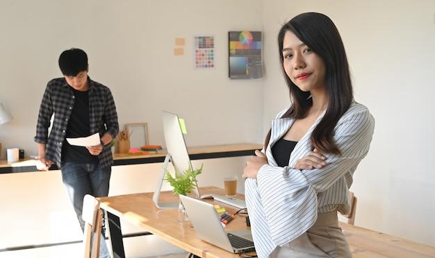 Vol vertrouwen vrouw die camera op creativiteitwerkplaats bekijkt.
