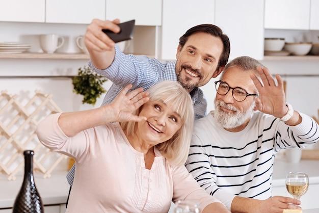 Vol vreugde. gelukkig jonge lachende man aan het eten en genieten van vrije tijd met zijn bejaarde ouders terwijl hij de mobiel vasthoudt en selfie maakt