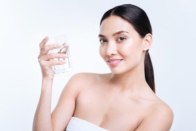 Voldoende waterniveau. mooie donkerharige jonge vrouw die een glas water houdt en glimlacht terwijl status geïsoleerd op een witte muur