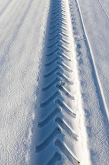 Volg autowiel op de witte echte sneeuw na sneeuwval. winter close-up.