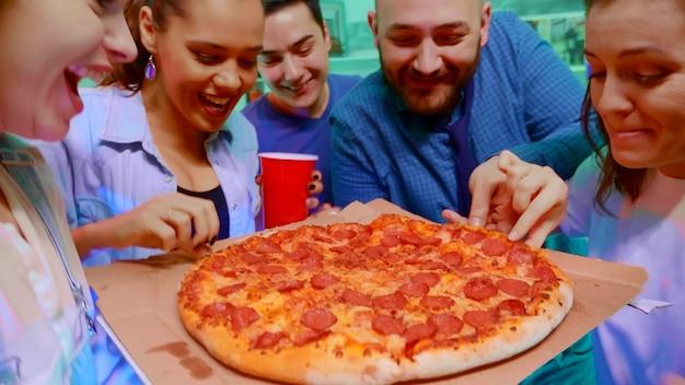Volg het shot van het meisje dat op het feest arriveert met heerlijke pizza voor haar vrienden. opgewonden groep mensen.