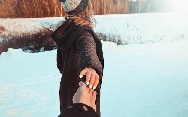 Volg me meisje met vriendje hand in winter sneeuw bos. vintage look, vakantie, romantische sfeer, liefde. winter witte bomen landschap.