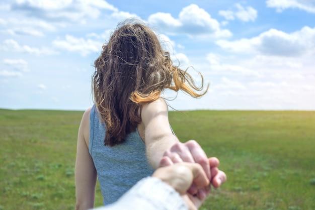 Volg mij, aantrekkelijk donkerbruin meisje dat de hand van de lood in een schoon groen gebied houdt, steppe met wolken