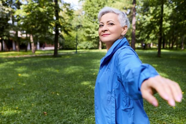 Volg mij. buiten beeld van gelukkig mooi grijs haired volwassen vrouw poseren in de wilde natuur terug te draaien met uitgestrekte arm, uitnodigend gebaar maken, gaan begeleiden door bos. hand onscherp