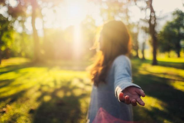 Volg mij, een mooie aziatische vrouw die elkaars hand vasthoudt en leidt naar het park voor zonsondergang