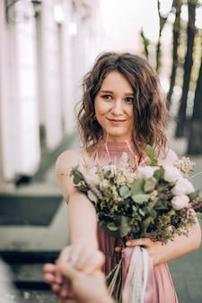 Volg mij! foto met bruid in roze jurk met een boeket van de bloem