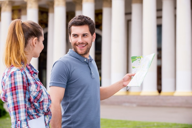 Volg mij! gelukkig jong toeristenpaar dat dichtbij mooi gebouw loopt terwijl de mens kaart houdt
