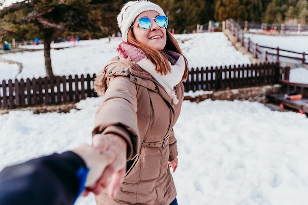 Volg mij. gelukkige vrouw en man hand in hand. pov. op de berg. liefde concept