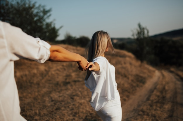 Volg mij. mooie jonge vrouw die in witte kleren hand houdt en haar vriend leidt om te lopen.
